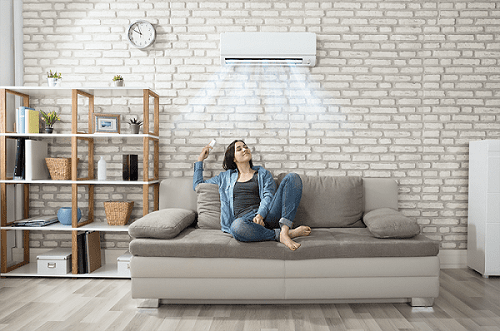 a woman enjoys air conditioning inside her home on her couch