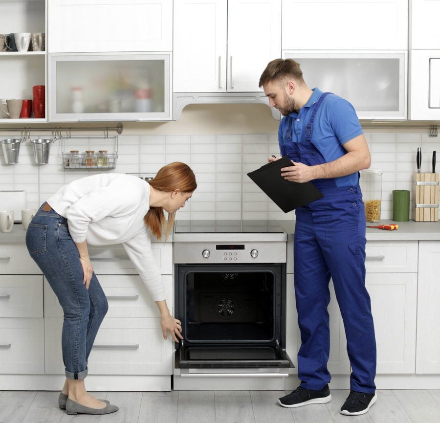 a repair man helps a woman with her residential oven
